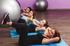 Frauen führen Übungen mit einem großen Ball für Eignung durch Stockbild