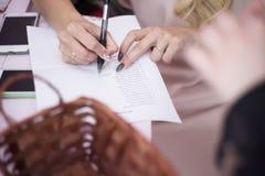 Frauen füllt die Liste auf dem Tisch Nahaufnahmehände lizenzfreie stockfotos