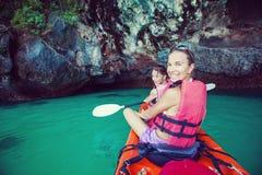 Frauen fahren in der hohen See am Krabi-Ufer, Thailand Kayak Stockfotos