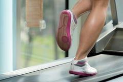 Frauen-Füße auf Tretmühle Lizenzfreie Stockbilder