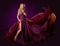 Frauen-Fliegen-purpurrotes Kleid, Mode-Modell Dancing im langen wellenartig bewegenden flatternden Kleid stockbild