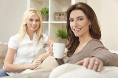Frauen-Freunde, die zu Hause Tee oder Kaffee trinken Lizenzfreie Stockfotos