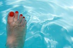 Frauen-Fuß im blauen Wasser lizenzfreies stockbild