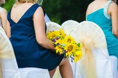 Frauen-Gast an der Hochzeit, die mit Sonnenblumen sitzt stockbild