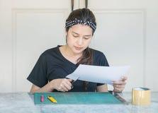 Frauen-Gebrauchsscheren der Nahaufnahme schnitten asiatische Papier für Kunstwerk auf Marmortabelle vor Haus lizenzfreies stockbild