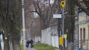 Frauen gehen entlang eine Stadtstraße hinter der Post der Zustandsfirma UkrPoshta Gelbes Logo auf einem Posten Briefkasten im Fi stock video