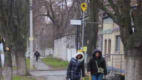 Frauen gehen entlang eine Stadtstraße hinter der Post der Zustandsfirma UkrPoshta Gelbes Logo auf einem Posten Briefkasten im Fi stock video footage