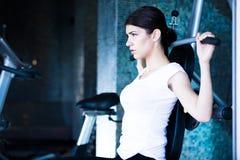Frauen-Gewicht-Training an der Gymnastik An trainieren ziehen Gewichtsmaschine herunter Frau, die ZugUPS ausübt anhebende Dummköp stockfotos