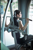 Frauen-Gewicht-Training an der Gymnastik An trainieren ziehen Gewichtsmaschine herunter Frau, die ZugUPS ausübt anhebende Dummköp stockfoto