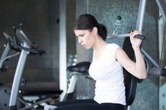 Frauen-Gewicht-Training an der Gymnastik An trainieren ziehen Gewichtsmaschine herunter Frau, die ZugUPS ausübt anhebende Dummköp stockbilder