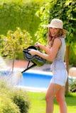 Frauen gießt Blumen im Garten mit Wasser Lizenzfreie Stockfotografie