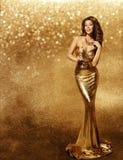 Frauen-Goldkleid, Mode-Modell, Champagne im langen goldenen Kleid stockfoto