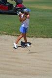 Frauen-Golfspieler, der aus Sand heraus schlägt Lizenzfreie Stockfotografie