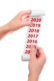 Frauen-Griff in ihrer Handrolle des Papiers mit gedruckt 2017, 2018, 2019, Konzept des neuen Jahr-2020 Stockbild