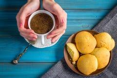 Frauen-Griff-Kaffee im Weinlesebecher in den Händen mit Schmutzlöffel und stockfotografie