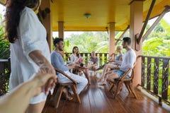 Frauen-Griff-Mann-Hand kommen Sommer-Terrasse mit der draußen sprechenden Leute-Gruppe, Freund-glückliches Lächeln Stockfotografie
