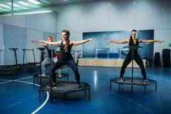 Frauen gruppieren das Handeln der geeigneten Übung auf Sporttrampoline Lizenzfreie Stockfotos