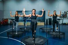 Frauen gruppieren das Handeln der geeigneten Übung auf Sporttrampoline Lizenzfreie Stockfotografie