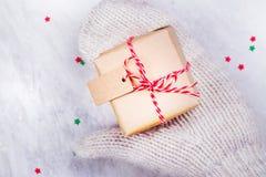 Frauen hält eine kleine Geschenkbox in den Händen, die in Weiß gestrickten Handschuhen getragen werden Lizenzfreies Stockfoto