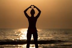Frauen-Hände, die ein Herz mit Sonnenuntergang-Schattenbild bilden Stockfotografie