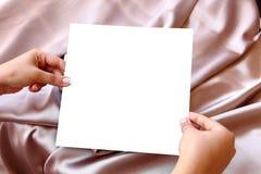 Frauen-Hände, die leeres Weißbuch halten Stockfotos