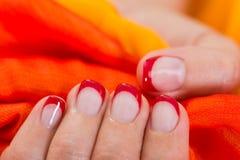 Frauen-Hände mit dem Nagel-Lack, der Gewebe hält Stockfotografie