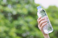 Frauen halten eine Flasche sauberes Trinkwasser an einem Park stockfoto