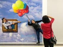 Frauen-Haltungen für eine Ballon-Illusion Stockfoto