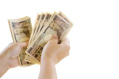 Frauen-Hand, die Banknote von 10.000 Japanern Yen Bills Isolate hält Lizenzfreies Stockfoto