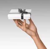 Frauen-Hand, die Feiertags-anwesenden weißen Kasten mit Grey Ribbon hält Stockbild