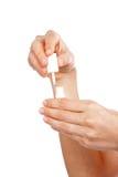 Frauen-Hand, die weißes Nailpolish hält Stockbilder