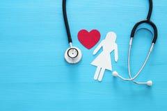 Frauen healf Versicherung Konzeptbild des Stethoskops und Frauenfigur auf Holztisch Beschneidungspfad eingeschlossen lizenzfreie stockfotografie