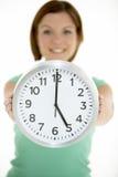 Frauen-Holding-Borduhr, die 5 Uhr zeigt Lizenzfreies Stockbild