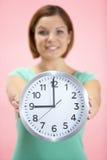 Frauen-Holding-Borduhr, die 9 Uhr zeigt Stockbilder
