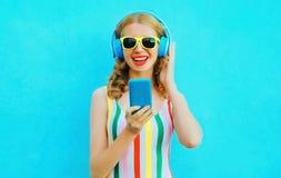 Frauen-Holdingtelefon des Porträts glückliches lächelndes, das Musik in den drahtlosen Kopfhörern auf buntem Blau hört stockfotografie