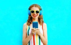 Frauen-Holdingtelefon des Portr?ts gl?ckliches l?chelndes, das Musik in den drahtlosen Kopfh?rern auf buntem Blau h?rt stockbilder