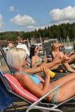 Ein Sonnenbad nehmende Frauen, die Lichtschutzbikini anwenden Lizenzfreie Stockbilder
