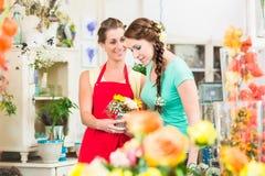 Frauen im Blumenspeicher die Rosen genießend Lizenzfreie Stockfotografie