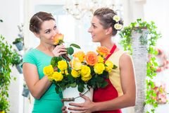 Frauen im Blumenspeicher die Rosen genießend Stockbild