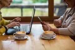 Frauen im Café mit Geräten Stockfoto