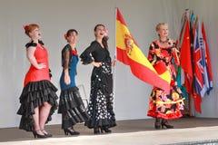 Frauen im Flamenco kleidet das Fliegen der spanischen Flagge lizenzfreie stockfotos
