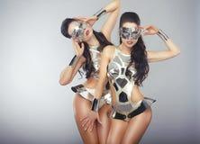 Frauen im funkelnden kosmischen Cyber-Kostüm-Gestikulieren Stockfoto