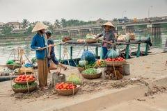 Frauen im konischen Hut und im Mann, die Boot entlädt Lizenzfreie Stockfotografie