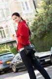 Frauen im roten Mantel auf der Straße lizenzfreie stockfotografie