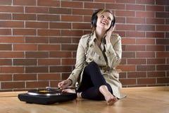 Frauen im trenchcoat hört Musik Lizenzfreie Stockfotos