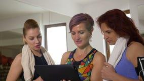 Frauen im Turnhallenstudio unter Verwendung der Tablette für Ausbildungsgewichtsverlustzeitplan stock footage
