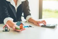 Frauen-Immobilienagenturgriff ein Modell des kleinen Hauses in ihrer Hand, bezüglich stockfotografie