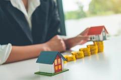 Frauen-Immobilienagenturgriff ein Modell des kleinen Hauses in ihrer Hand und lizenzfreie stockbilder