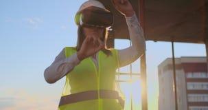 Frauen-Ingenieur Builder auf dem Dach des Gebäudes auf Sonnenuntergangständen in VR-Gläsern und -bewegungen seine Hände unter Ver stock video footage