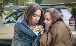 Frauen innerhalb der Schlafsäcke, die Kaffeetasse halten Stockbild